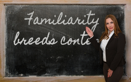 Successful, beautiful and confident woman showing Familiarity breeds contempt on blackboard photo