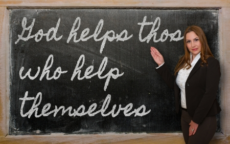 helps: Successful, beautiful and confident woman showing God helps those who help themselves on blackboard