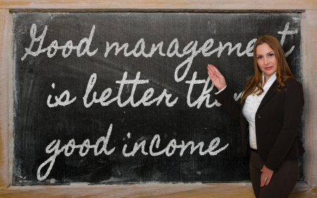 than: Successful, beautiful and confident woman showing Good management is better than good income on blackboard