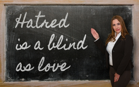 Successful, beautiful and confident woman showing Hatred is a blind as love on blackboard photo