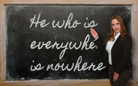 Successful, beautiful and confident woman showing He who is everywhere is nowhere on blackboard Stock Photo - 18417007