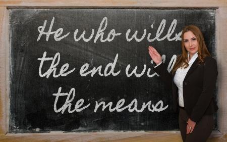Successful, beautiful and confident woman showing He who wills the end wills  the means on blackboard Stock Photo - 18416950