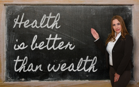 than: Successful, beautiful and confident woman showing Health is better than wealth on blackboard Stock Photo