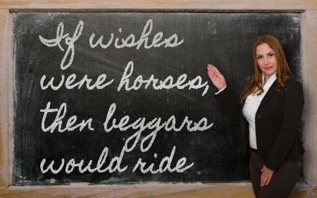 Successful, beautiful and confident woman showing If wishes were horses, then beggars would ride on blackboard