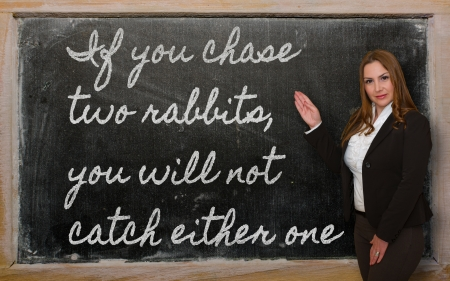 either: Successful, beautiful and confident woman showing If you chase two rabbits, you will not catch either on blackboard Stock Photo