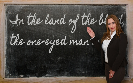 Successful, beautiful and confident woman showing In the land of the blind, the one-eyed man is king on blackboard Stock Photo