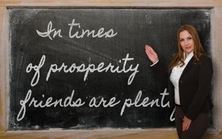 plentiful: Successful, beautiful and confident woman showing In times of prosperity friends are plentiful on blackboard Stock Photo