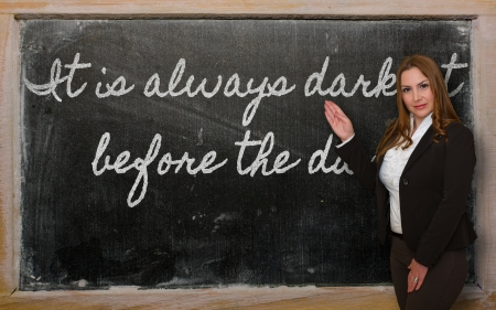 Successful, beautiful and confident woman showing It is always darkest before the dawn on blackboard Stok Fotoğraf - 18417019