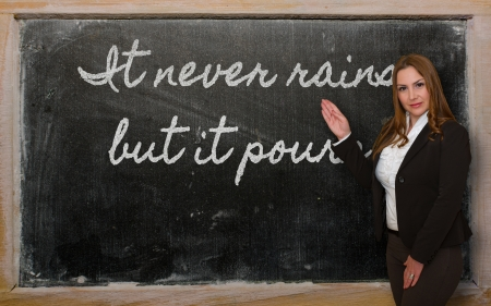 rains: Successful, beautiful and confident woman showing It never rains but it pours on blackboard Stock Photo