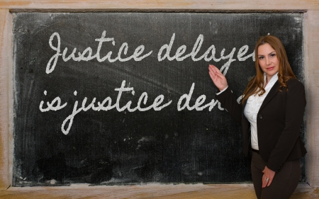 delayed: Successful, beautiful and confident woman showing Justice delayed is justice denied on blackboard