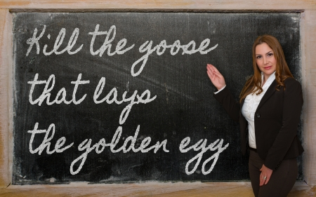 Successful, beautiful and confident woman showing Kill the goose that lays the golden egg on blackboard Stock Photo