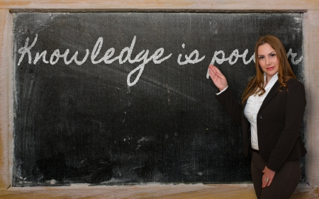 Successful, beautiful and confident woman showing Knowledge is power on blackboard photo