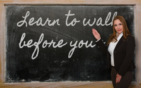 Successful, beautiful and confident woman showing Learn to walk before you run on blackboard Stok Fotoğraf - 18417030