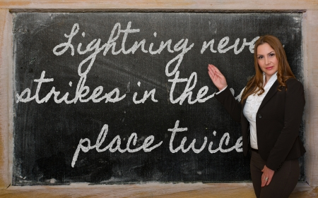 Successful, beautiful and confident woman showing Lightning never strikes in the same place twice on blackboard Фото со стока