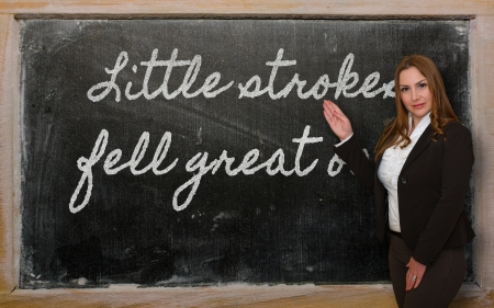 fell: Successful, beautiful and confident woman showing Little strokes fell great oaks on blackboard
