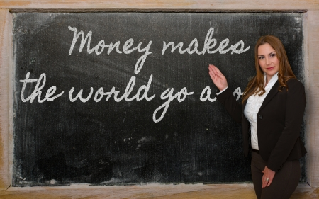 Successful, beautiful and confident woman showing Money makes the world go around on blackboard Stock Photo - 18416996