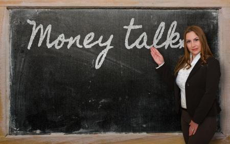 conversa: Mujer exitosa, bella y segura mostrando dinero habla sobre la pizarra