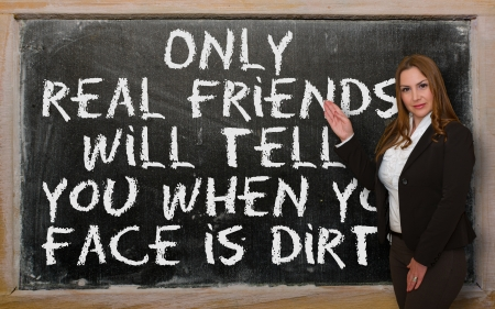 Successful, beautiful and confident woman showing Only real friends will tell you when your face is on blackboard Stock Photo - 18417058