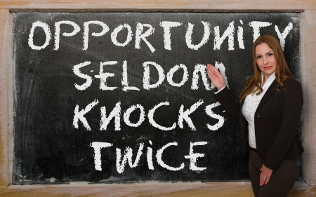 twice: Successful, beautiful and confident woman showing Opportunity seldom knocks twice on blackboard Stock Photo