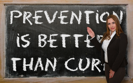 cure prevention: Successful, beautiful and confident woman showing Prevention is better than cure on blackboard