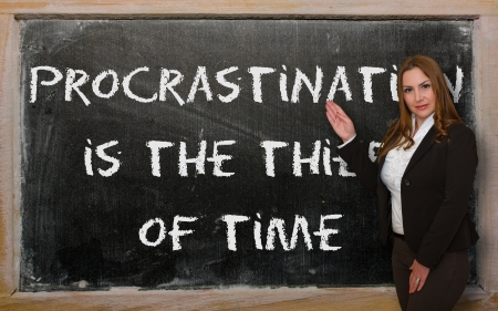 succesful woman: Successful, beautiful and confident woman showing Procrastination is the thief of time on blackboard Stock Photo