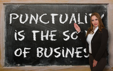 punctuality: Successful, beautiful and confident woman showing Punctuality is the soul of business on blackboard Stock Photo