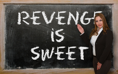 revenge: Successful, beautiful and confident woman showing revenge is sweet on blackboard Stock Photo
