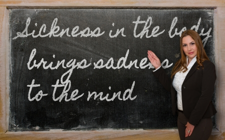 brings: Successful, beautiful and confident woman showing Sickness in the body brings sadness to the mind on blackboard