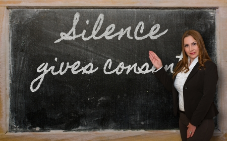 consent: Successful, beautiful and confident woman showing Silence gives consent on blackboard