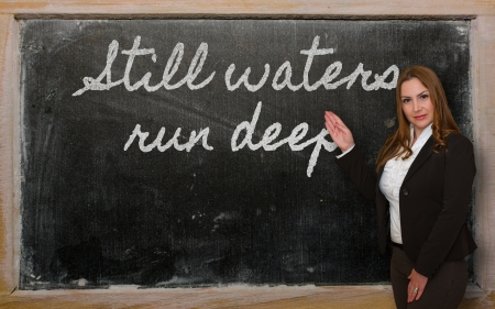 Successful, beautiful and confident woman showing Still waters run deep on blackboard