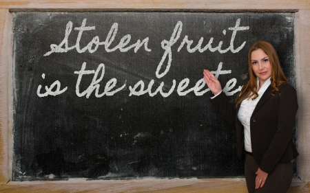sweetest: Successful, beautiful and confident woman showing Stolen fruit is the sweetest on blackboard Stock Photo