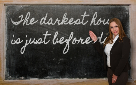 Successful, beautiful and confident woman showing The darkest hour is just before dawn on blackboard Stok Fotoğraf - 18416957