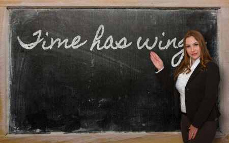 has: Successful, beautiful and confident woman showing Time has wings on blackboard