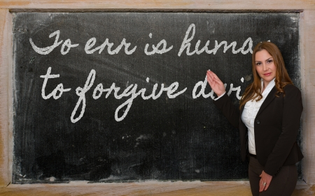 err: Successful, beautiful and confident woman showing To err is human, to forgive divine on blackboard