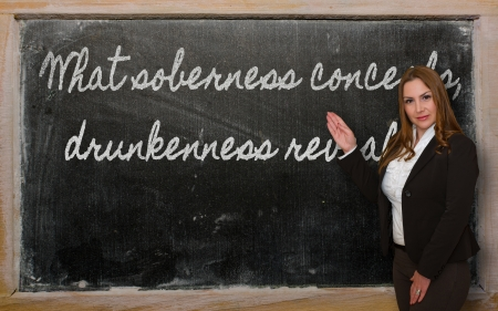 drunkenness: Successful, beautiful and confident woman showing What soberness conceals, drunkenness reveals on blackboard Stock Photo