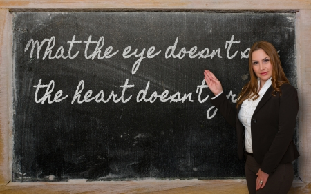 grieve: Successful, beautiful and confident woman showing What the eye doesn t see, the heart doesn t grieve on blackboard