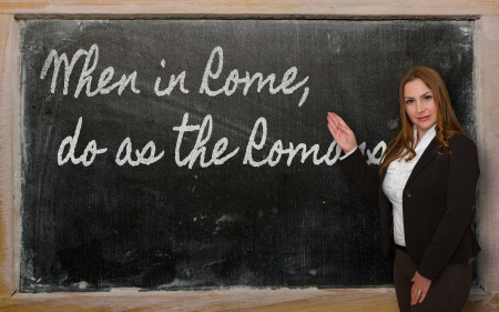 Successful, beautiful and confident woman showing When in Rome, do as the Romans do on blackboard Stock Photo - 18417004