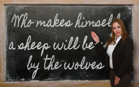 himself: Successful, beautiful and confident woman showing Who makes himself a sheep will be eaten by the wolves on blackboard