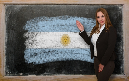 Successful, beautiful and confident woman showing flag of Argentina on blackboard for marketing research, presentation and tourist advertising photo