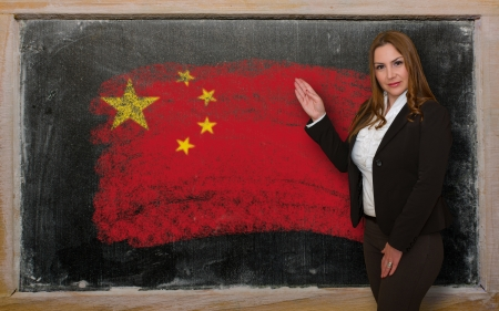 Successful, beautiful and confident woman showing flag of China on blackboard for marketing research, presentation and tourist advertising photo
