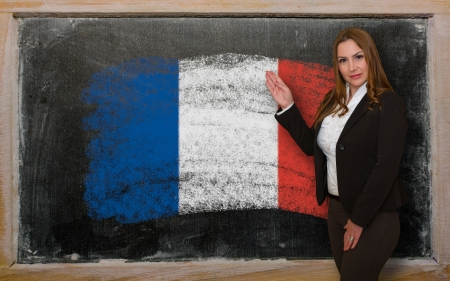 Successful, beautiful and confident woman showing flag of France on blackboard for marketing research, presentation and tourist advertising photo