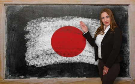 Successful, beautiful and confident woman showing flag of Japan on blackboard for marketing research, presentation and tourist advertising photo