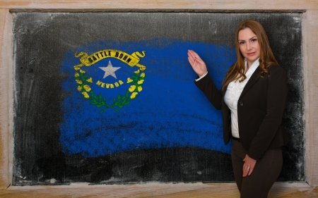 Successful, beautiful and confident woman showing flag of nevada on blackboard for marketing research, presentation and tourist advertising Stock Photo - 18632076