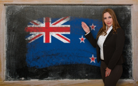 Successful, beautiful and confident woman showing flag of New Zealand on blackboard for marketing research, presentation and tourist advertising photo