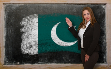 Successful, beautiful and confident woman showing flag of Pakistan on blackboard for marketing research, presentation and tourist advertising photo