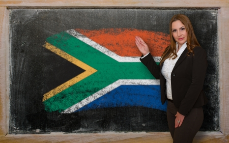 Successful, beautiful and confident woman showing flag of South Africa on blackboard for marketing research, presentation and tourist advertising photo