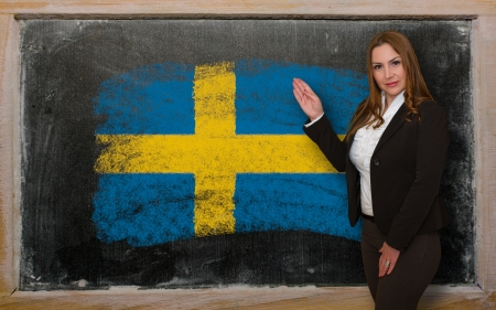 education in sweden: Successful, beautiful and confident woman showing flag of Sweden on blackboard for marketing research, presentation and tourist advertising Stock Photo