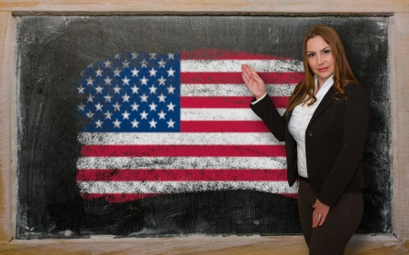 Successful, beautiful and confident woman showing flag of USA on blackboard for marketing research, presentation and tourist advertising photo