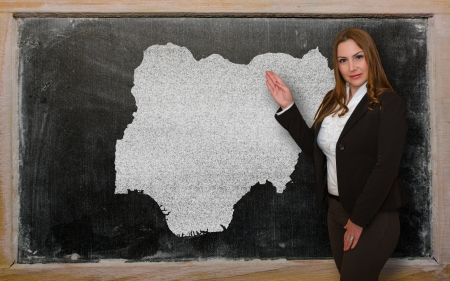 Successful, beautiful and confident young woman showing map of nigeria on blackboard for presentation, marketing research and tourist advertising photo