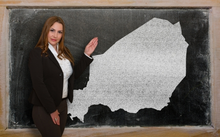 Successful, beautiful and confident young woman showing map of niger on blackboard for presentation, marketing research and tourist advertising photo